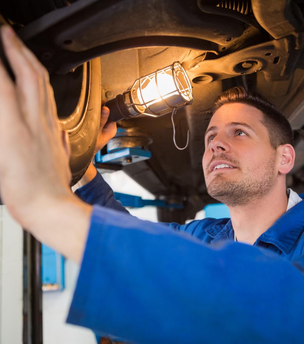Mechanic using torch to look under car at the repair garage - MOT Leighton Buzzard